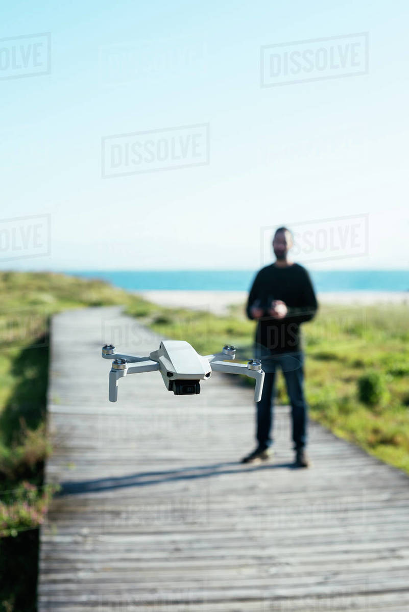 Young man flying a dron near to the beach Royalty-free stock photo