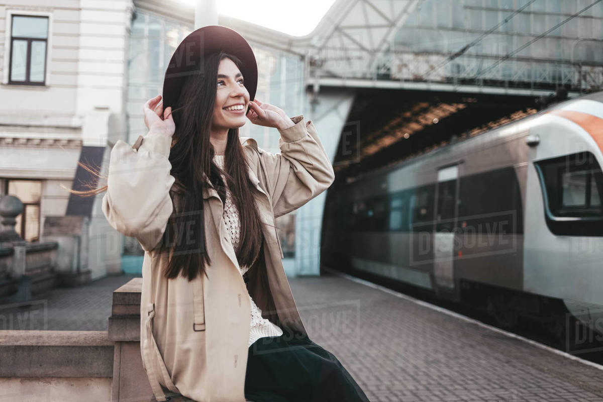 Smiling girl in hat at train station waiting for train departure Royalty-free stock photo