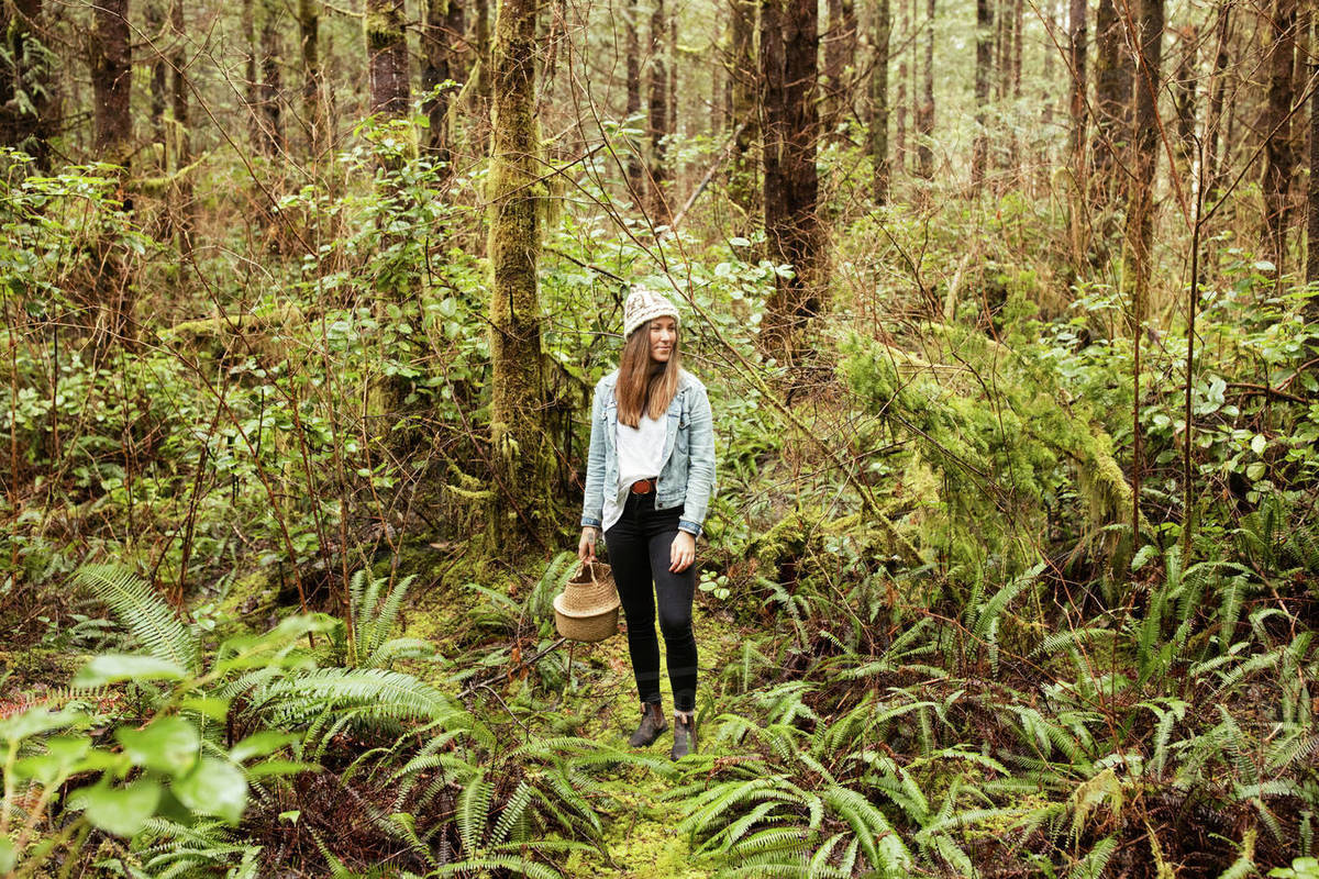 Beautiful woman forages in the rainforest near Tofino Royalty-free stock photo