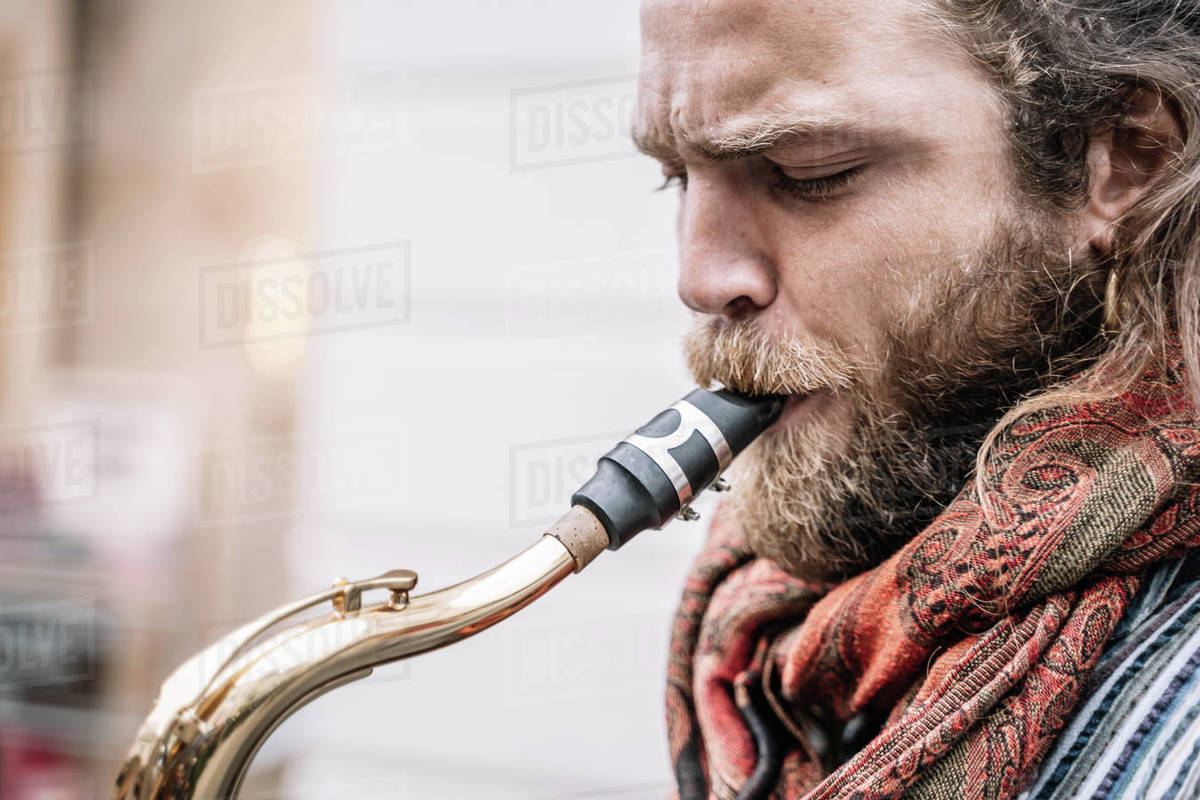 Face of saxophonist with long hair and beard playing in the street Royalty-free stock photo
