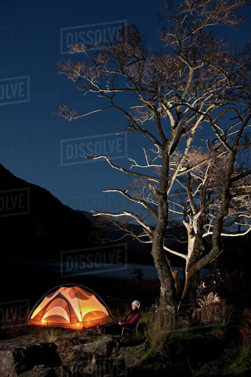 Female hiker sitting outside her tent at camp in North Wales Royalty-free stock photo