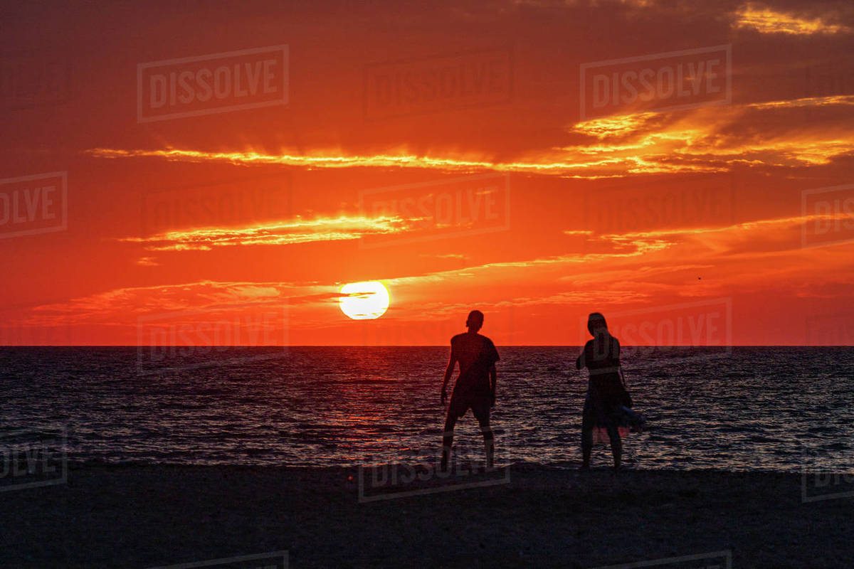 Silhouetted couple enjoying the sunset on the beach. Royalty-free stock photo
