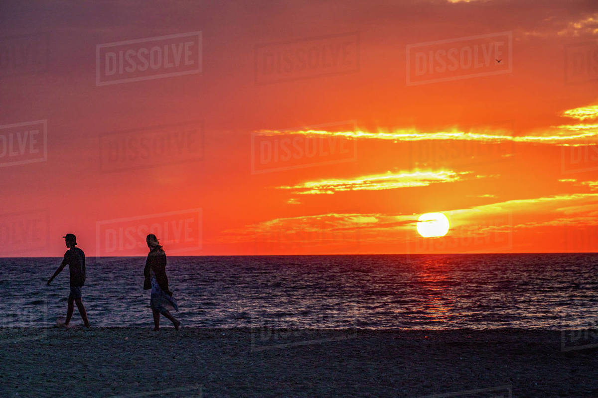 Young couple silhouette walking the beach as sun sets under a red sky. Royalty-free stock photo