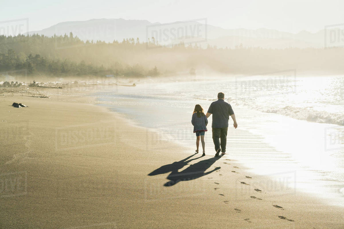 Father and daughter walking along beach at sunset Royalty-free stock photo