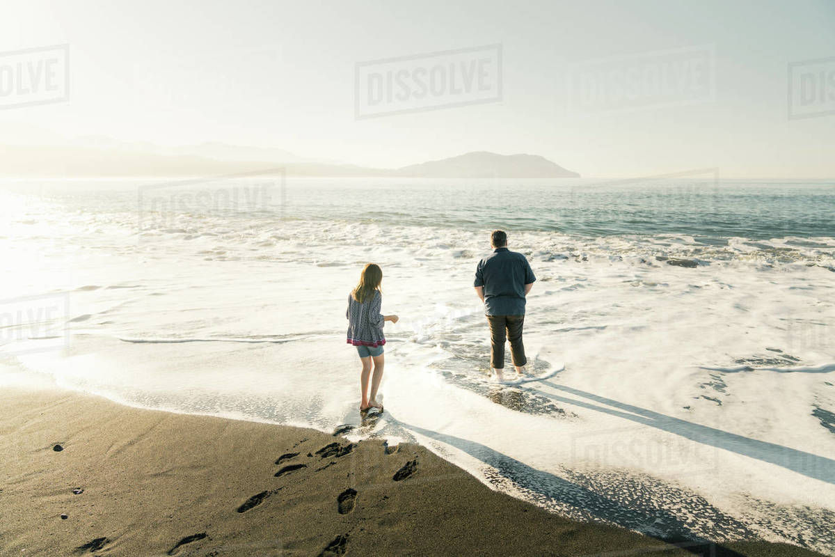 Father and daughter walking in water at the beach during sunset Royalty-free stock photo