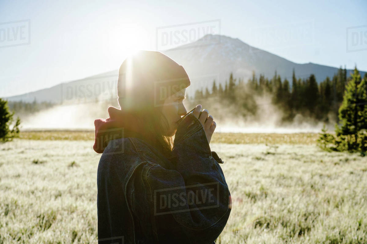 Young woman drinking coffee at sunrise near foggy mountain Royalty-free stock photo