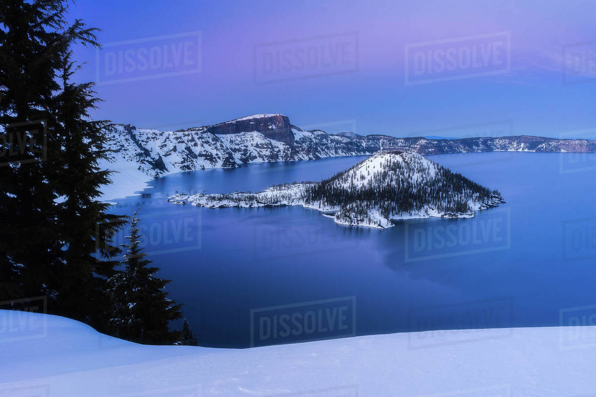 Crater lake and wizard island in the snow at sunset Royalty-free stock photo