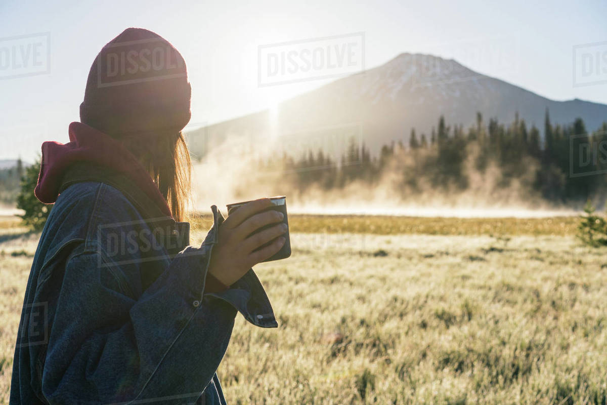 Young woman holding coffee at sunrise looking at foggy mountain Royalty-free stock photo