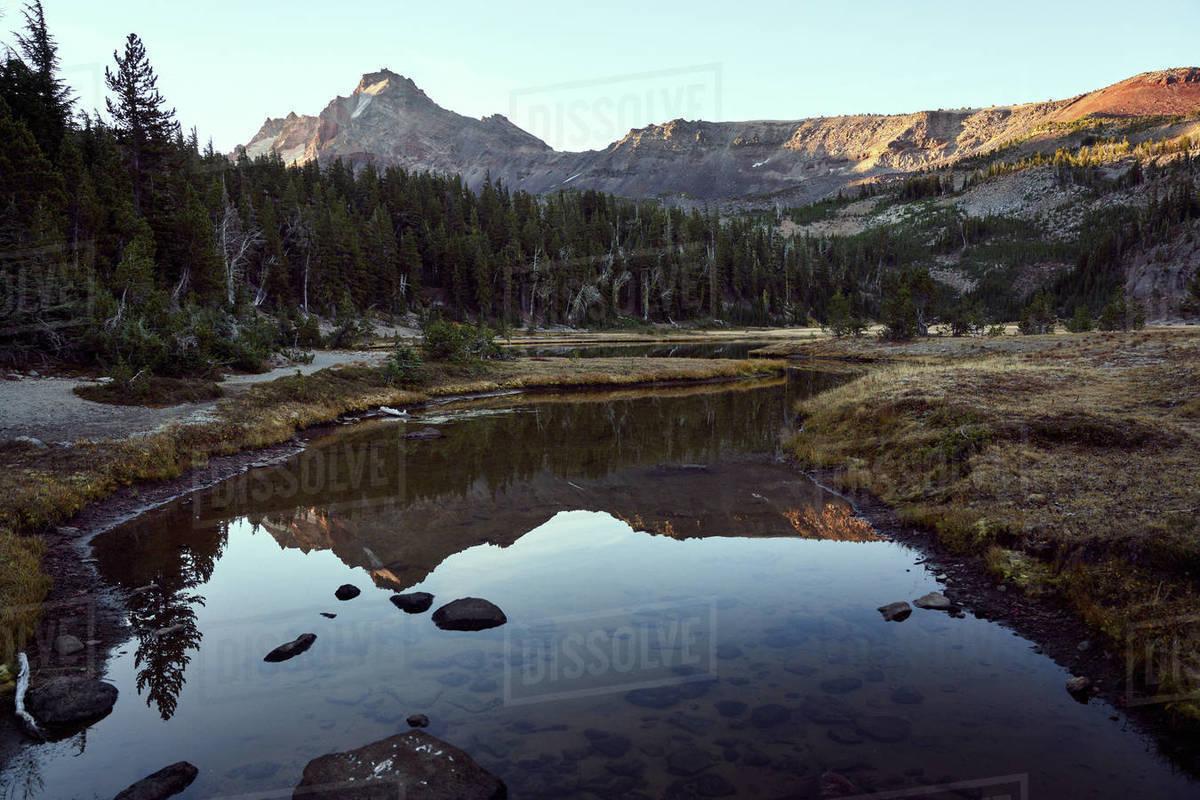 Creek winding towards mountain at sunset Royalty-free stock photo