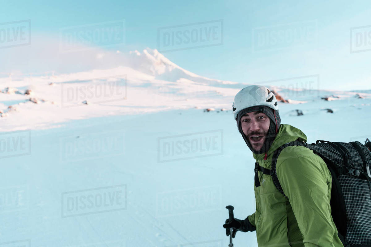 Skier looking at camera smiling while skinning up mountain Royalty-free stock photo