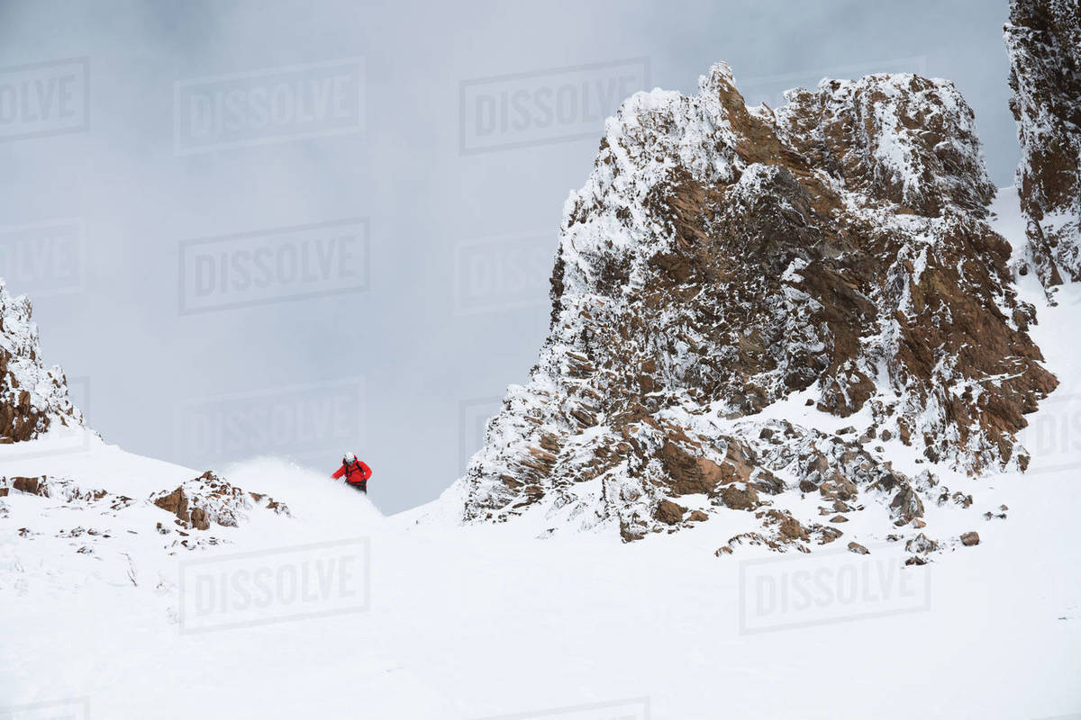 Snowboarder in red jacket making a turn in the mountains Royalty-free stock photo