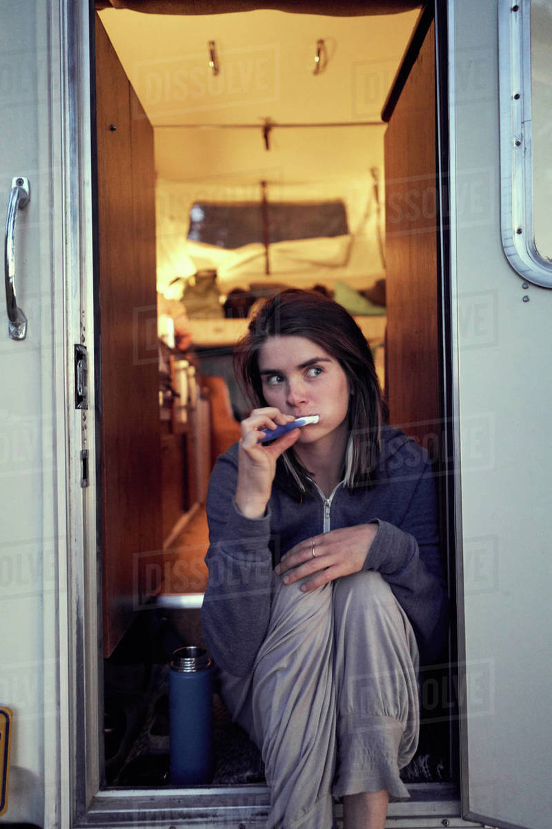 Young woman sitting in camper brushing teeth Royalty-free stock photo