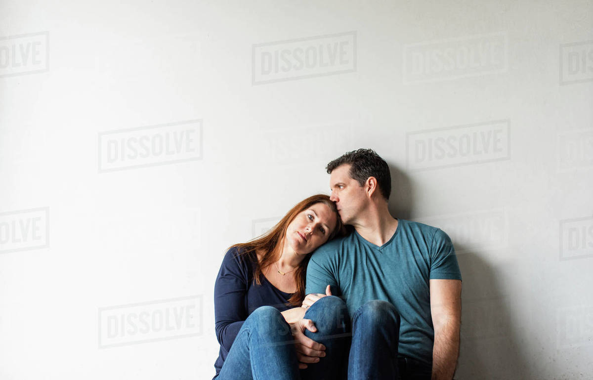 Cropped image of loving couple sitting together against a white wall. Royalty-free stock photo
