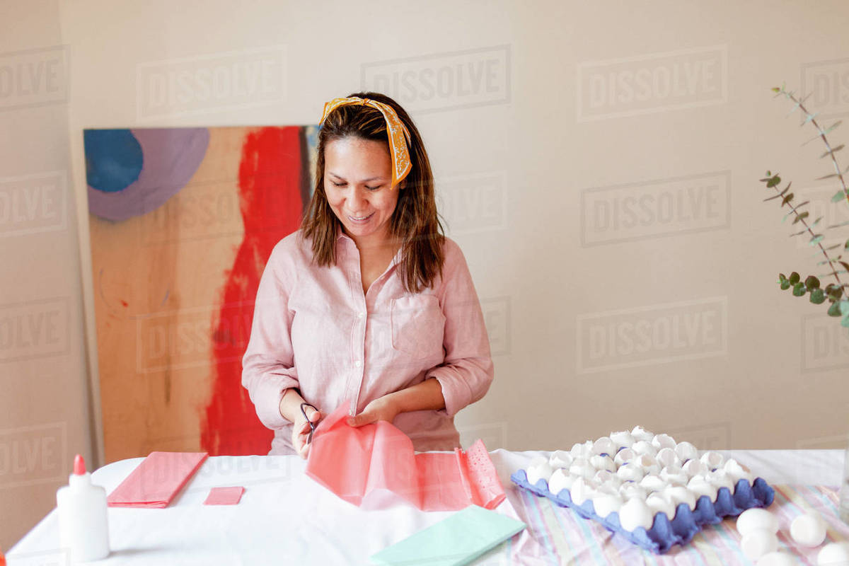 Happy woman cutting craft pink paper by eggshells at home Royalty-free stock photo