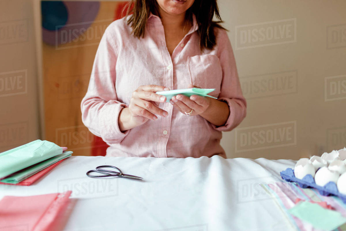 Cropped lady folding craft paper during tutorial during quarantine Royalty-free stock photo
