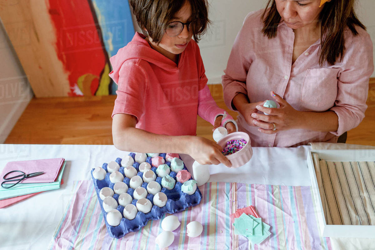 Mom teaching son how to make confetti eggs during homeshooling Royalty-free stock photo