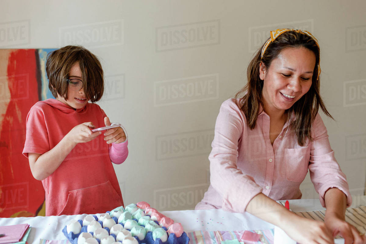 Happy mom working in a project while son is taking photo Royalty-free stock photo