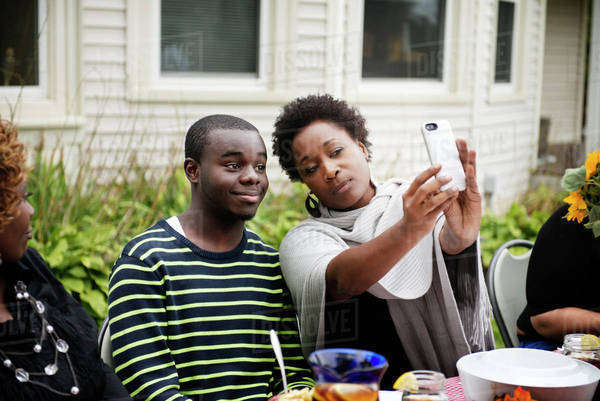 Woman and teenage boy taking selfie at dinner table Royalty-free stock photo