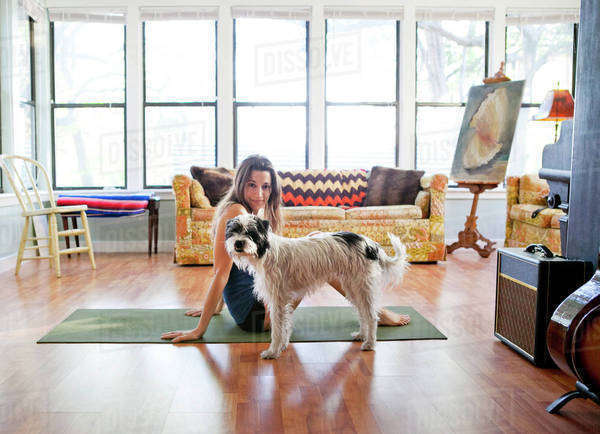 Woman on yoga mat with dog in living room Royalty-free stock photo