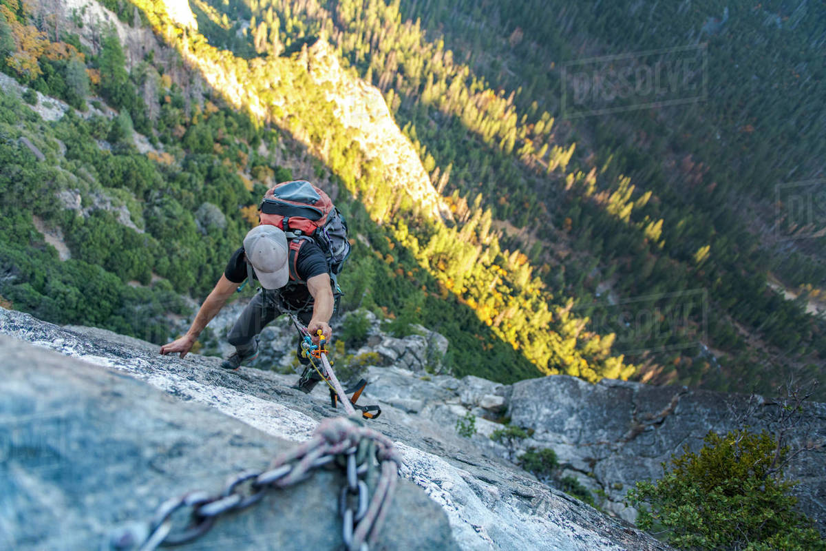 Man with hat looking down jugging rope up with backpack on El Capitan Royalty-free stock photo
