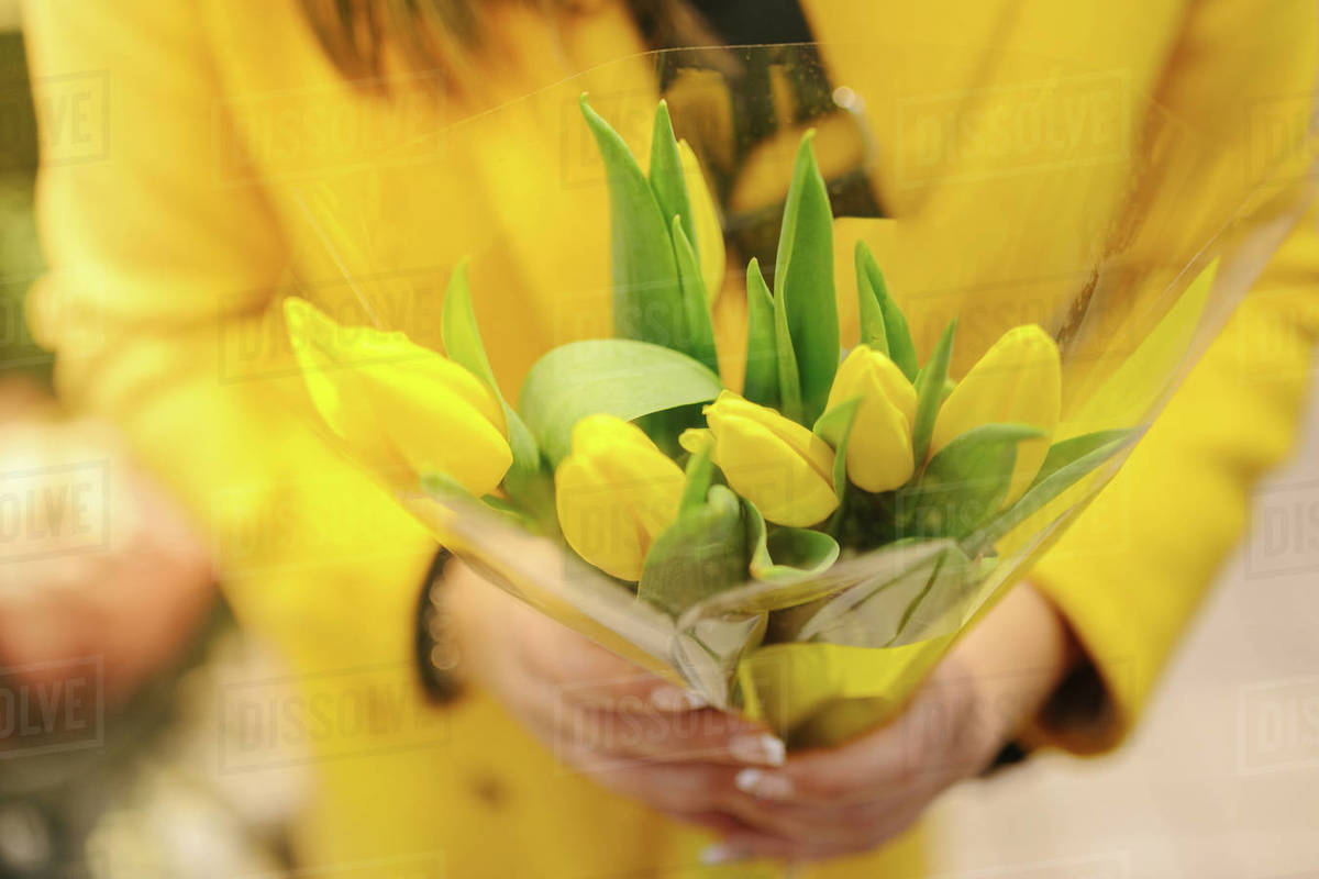 Unrecognizable woman with a bouquet of yellow tulips. She just receive Royalty-free stock photo