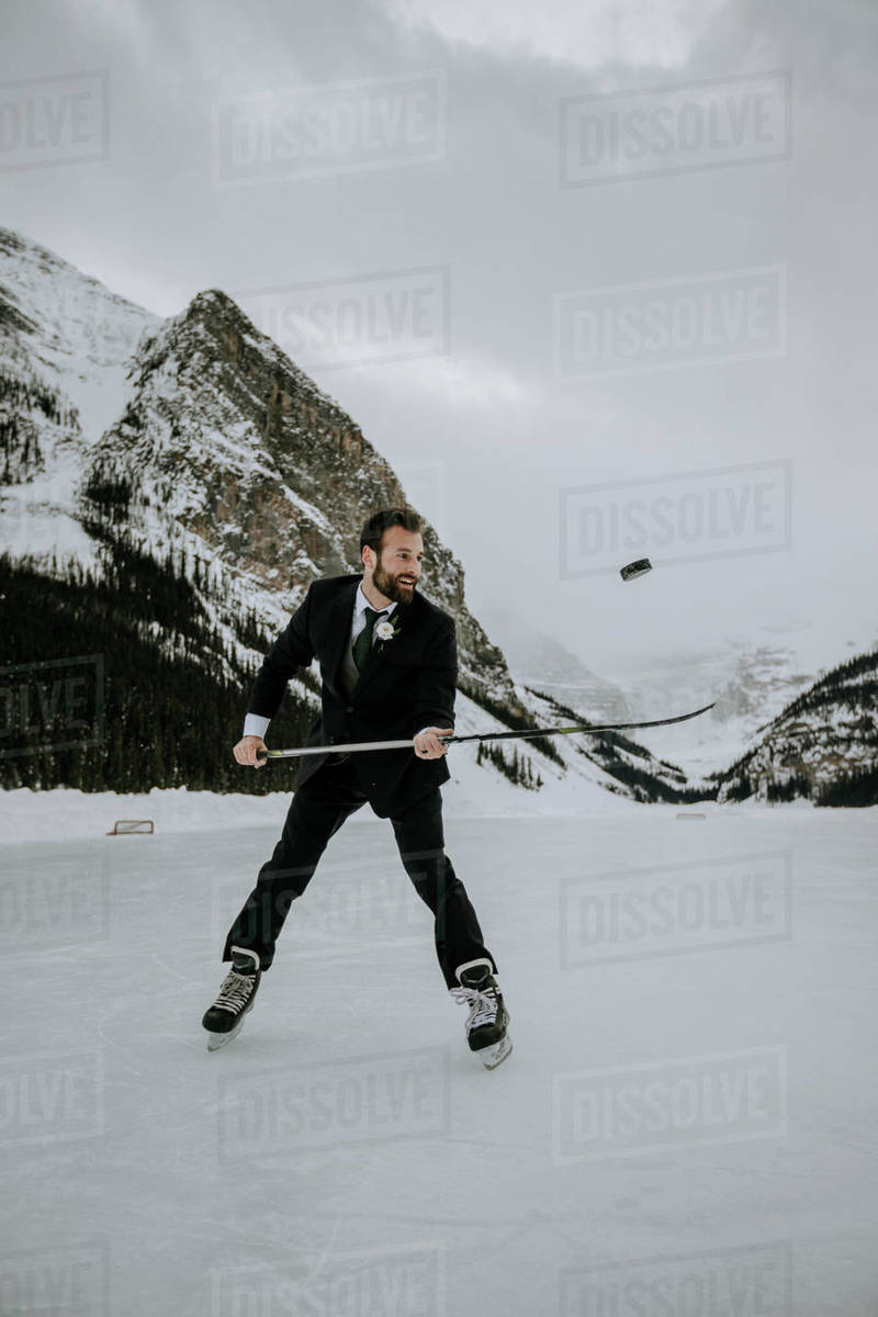 Hockey player with suit on juggles puck on frozen lake in mountains Royalty-free stock photo