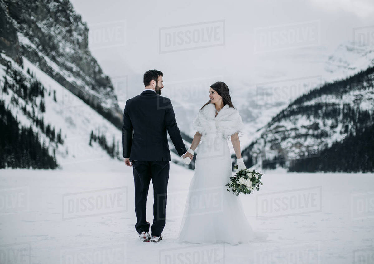 Bride and groom wedding on ice in winter Lake Louise, Alberta, Canada Royalty-free stock photo