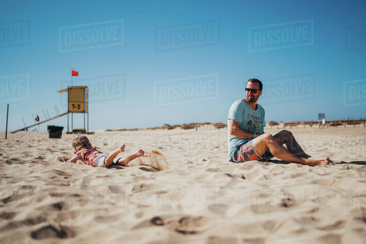 Father and child playing a the beach on a sunny day Royalty-free stock photo