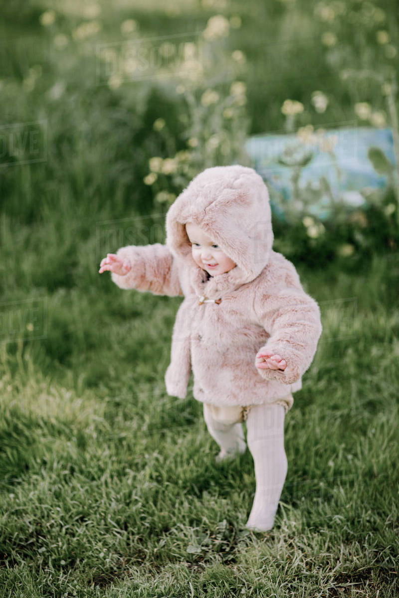 Baby girl first steps in pink fur coat outside on grass Royalty-free stock photo