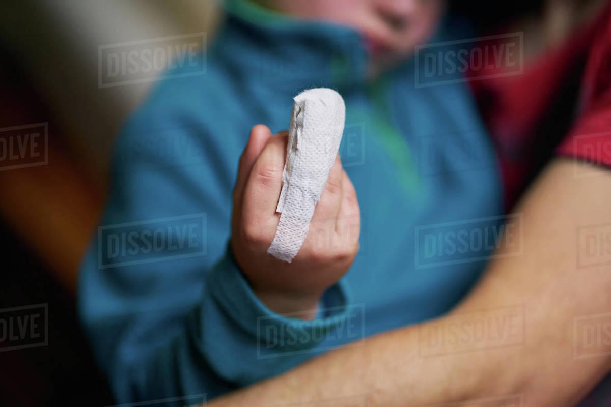 Crop child showing bandaged finger Royalty-free stock photo