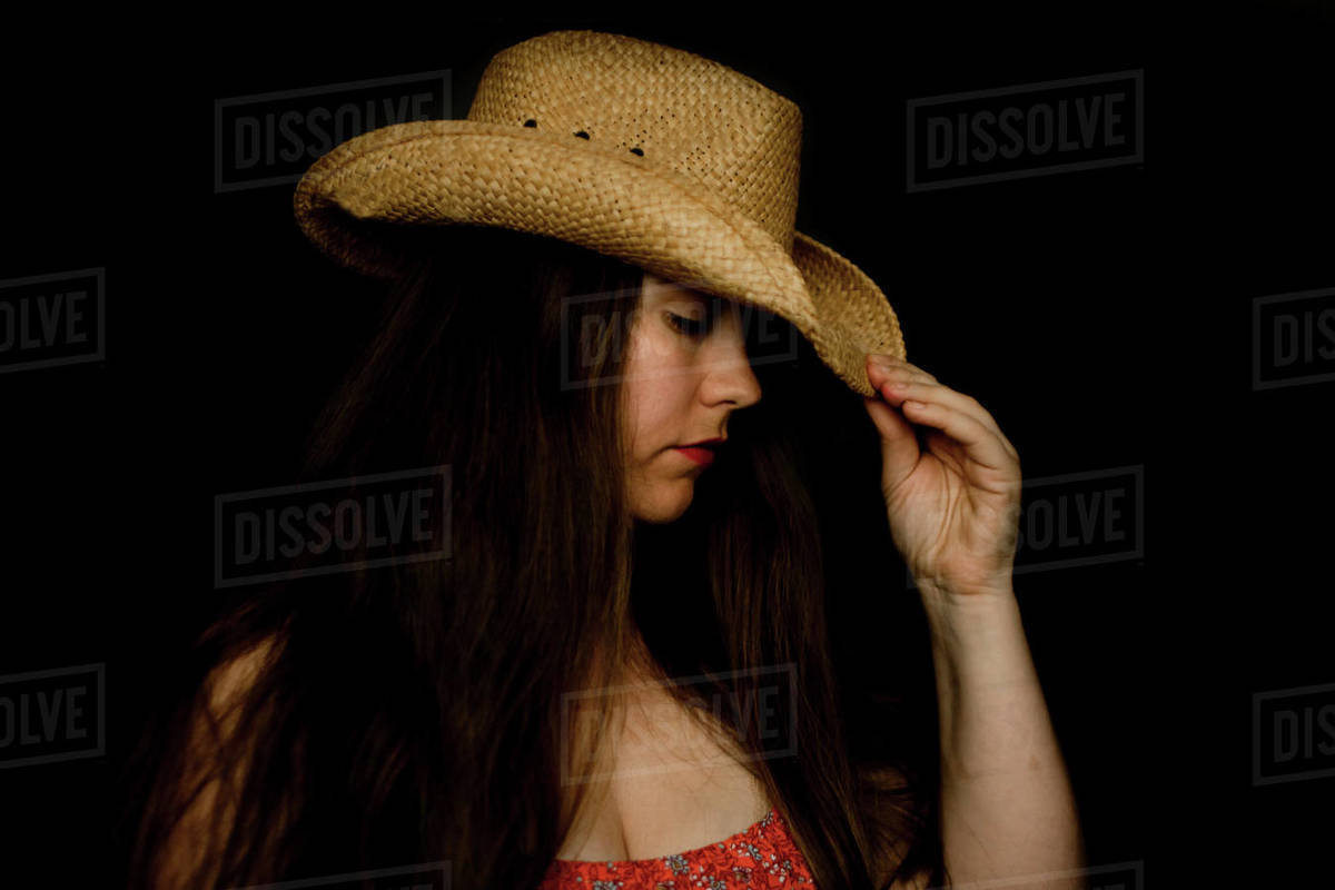 Sad lady in cowboy hat tipping her hat down in dramatic light Royalty-free stock photo