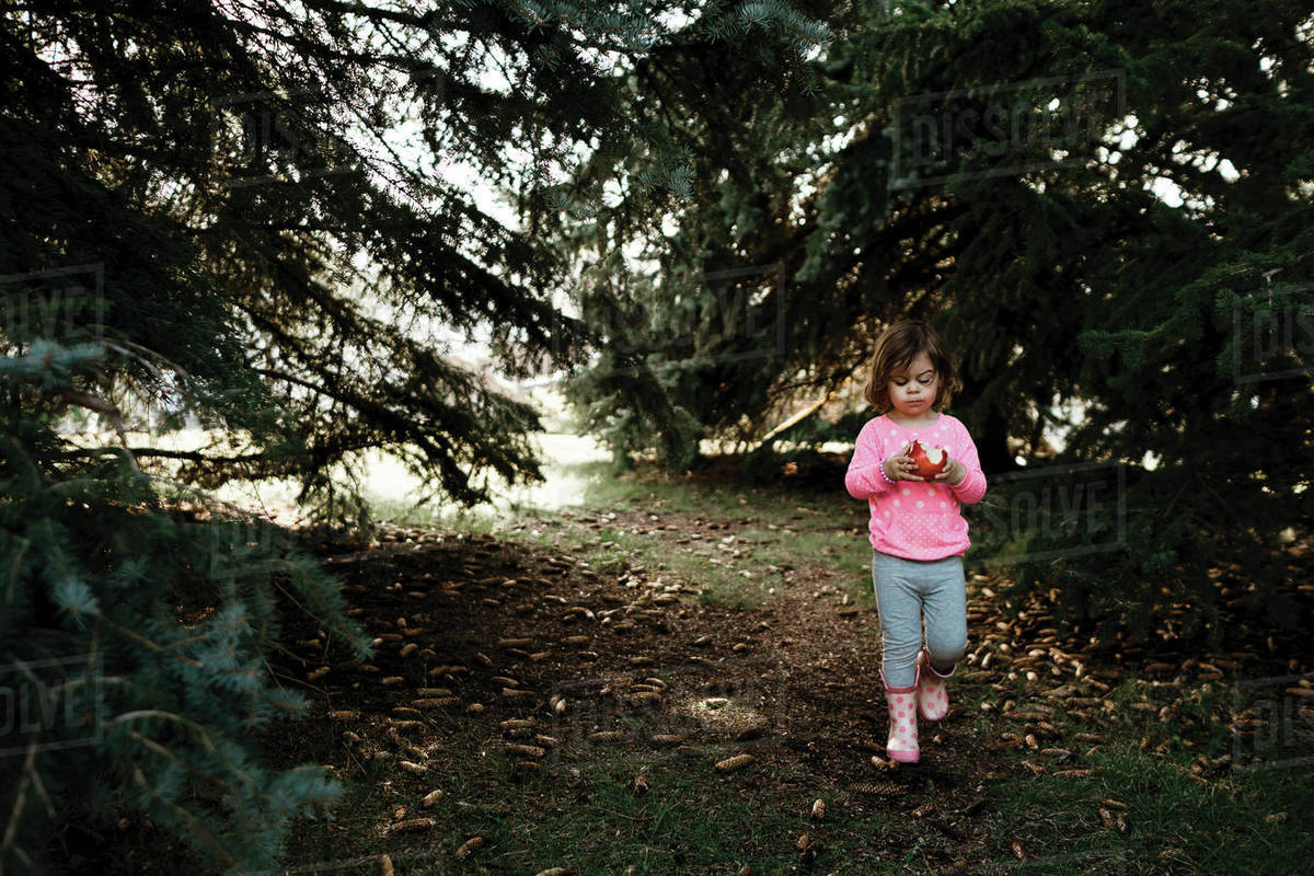 Young girl eating a red apple walking through a row of pine trees Royalty-free stock photo