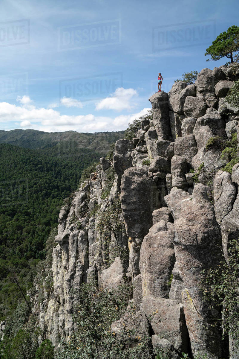 One woman standing on a high rock formation watching the landscape Royalty-free stock photo