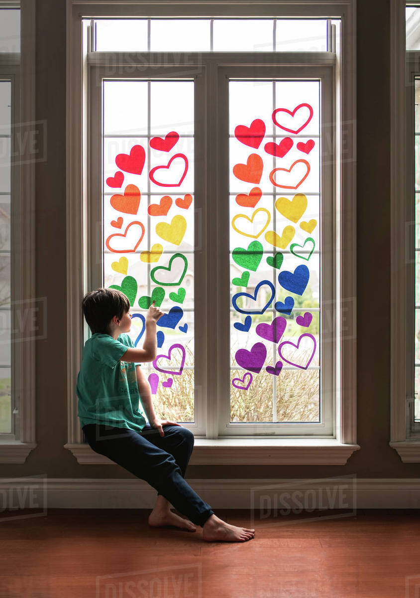 Boy sitting on sill of a window covered in a rainbow of paper hearts. Royalty-free stock photo
