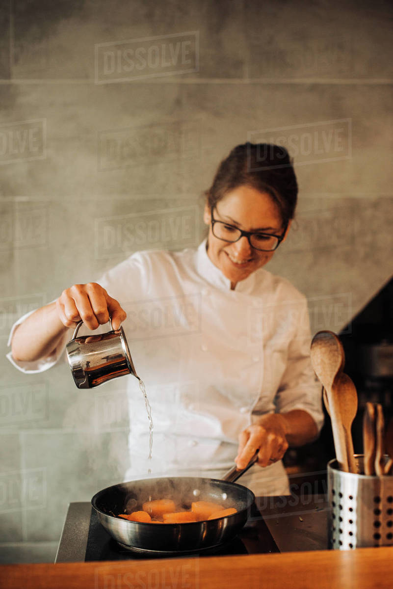 Female chef is adding water to cooking food Royalty-free stock photo