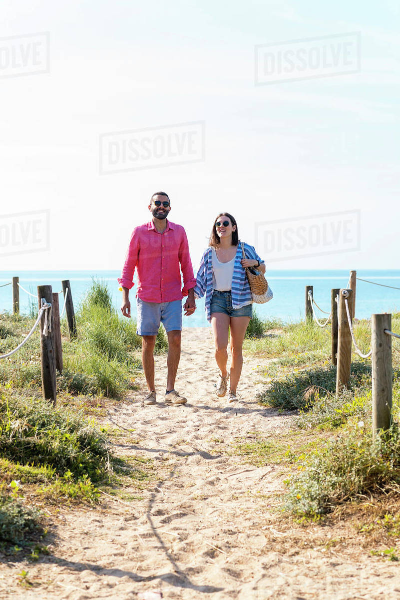 Happy couple with sunglasses holding hands while walking on beach Royalty-free stock photo