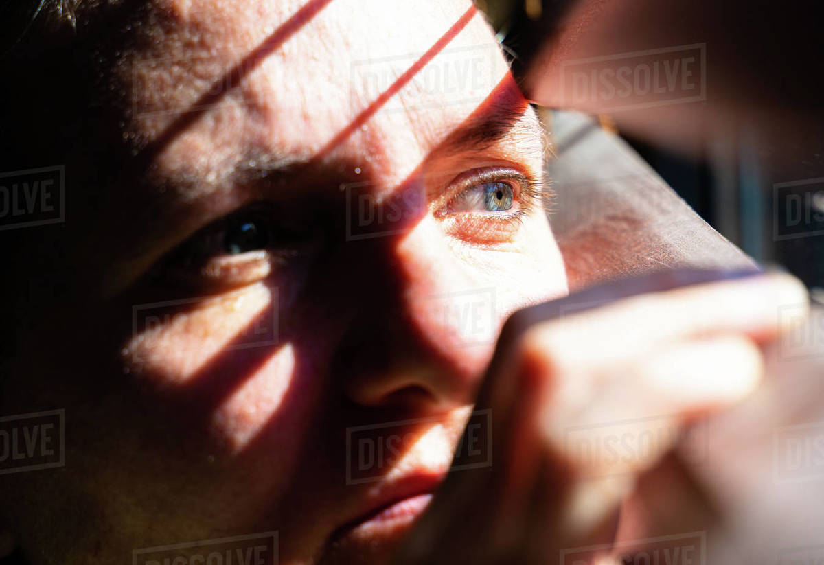 Adult woman with blue eyes opening a wooden curtain with her fingers to look through the window while the sunlight creates sun and shadow on her face. Horizontal photo. Royalty-free stock photo
