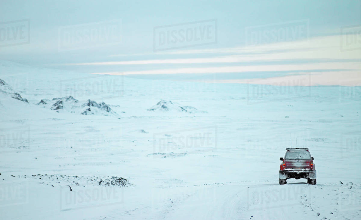 Red SUV driving through winter landscape in Iceland Royalty-free stock photo