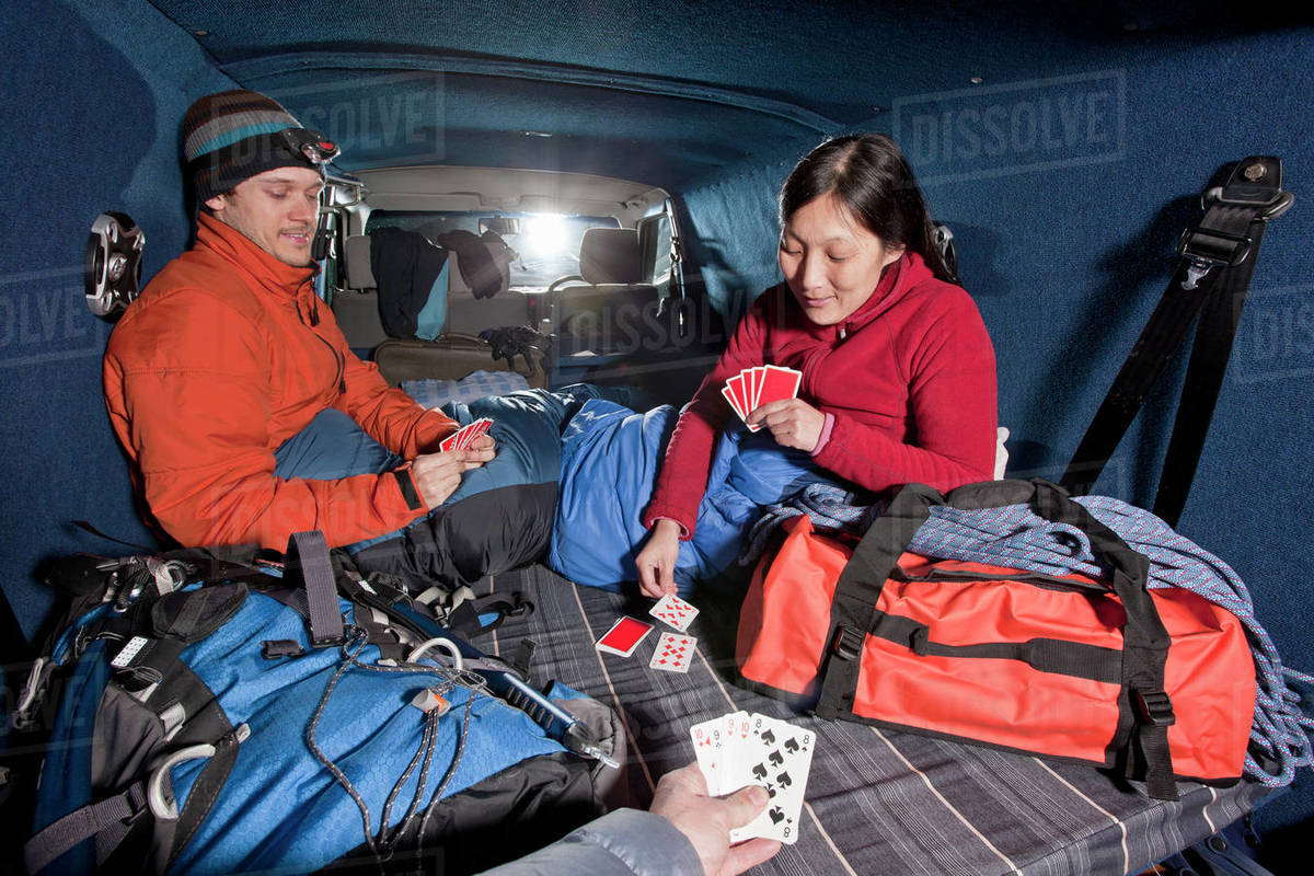 Couple playing cards in the back of a camper van Royalty-free stock photo