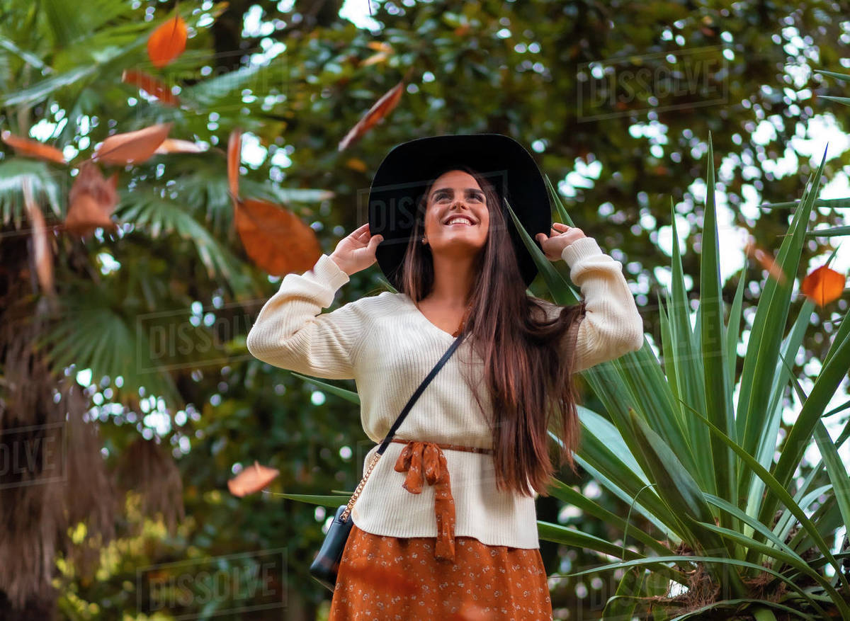 A young brunette in a fall photo session with falling tree leaves Royalty-free stock photo