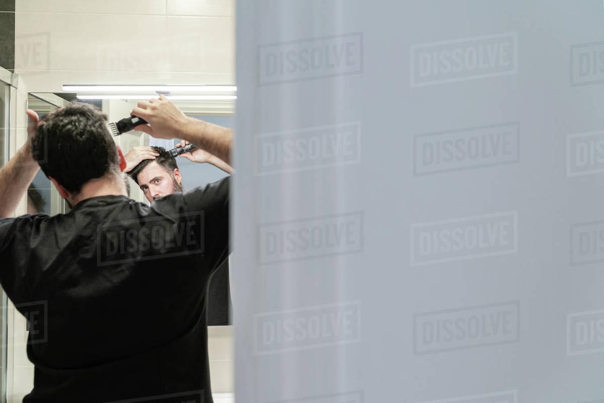 Self haircut. A man is cutting his hair with a hair clipper in the bathroom Royalty-free stock photo