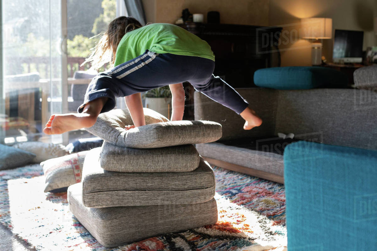 Child jumping over a pile of couch cushion pillows in living room Royalty-free stock photo