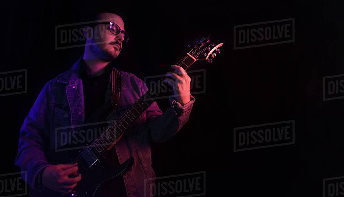 Young adult plays electric guitar under colored lights Royalty-free stock photo