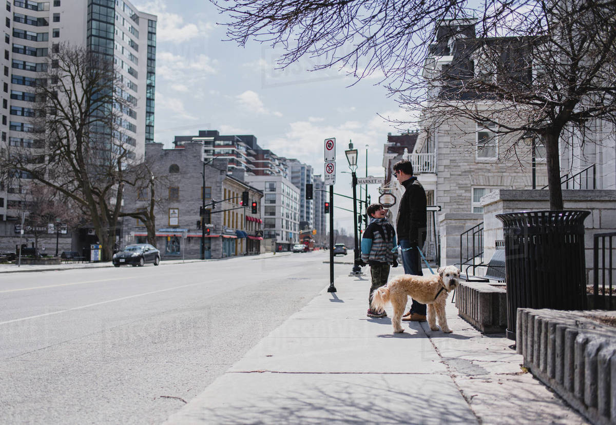 Father and son with dog standing on sidewalk of a quiet city street. Royalty-free stock photo
