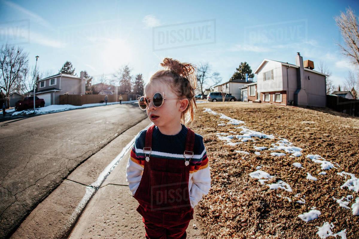 Young girl looking away standing on sidewalk in neighborhood Royalty-free stock photo