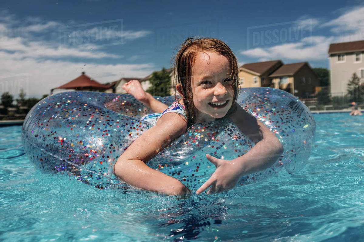 Center shot of young girl floating in neighborhood pool Royalty-free stock photo