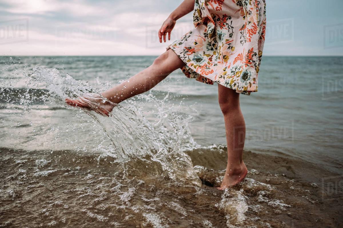 Young girl in dress splashing water in lake Michigan Royalty-free stock photo
