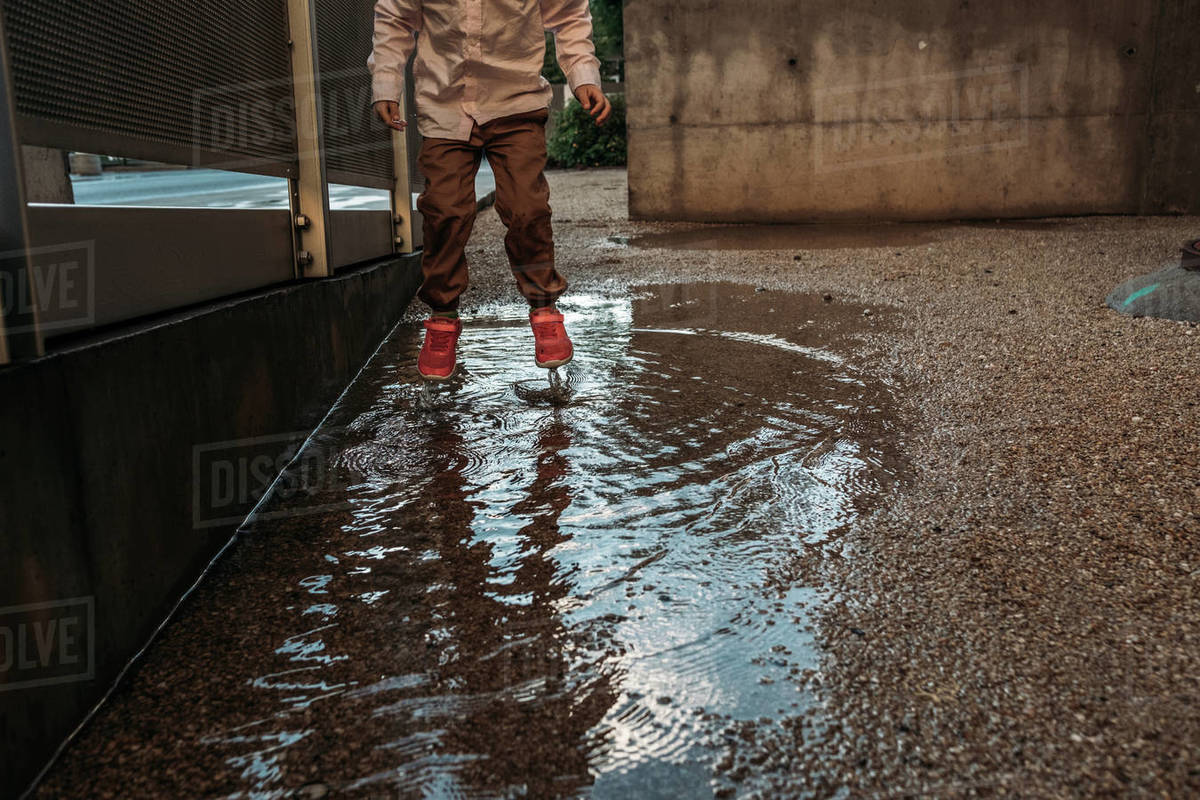 Young child jumping in puddle with pink shoes on Royalty-free stock photo