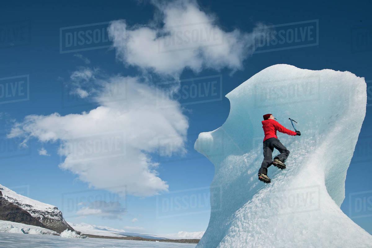 Woman climbinbg iceberg on the Fjallsjoull glacier lagoon Royalty-free stock photo