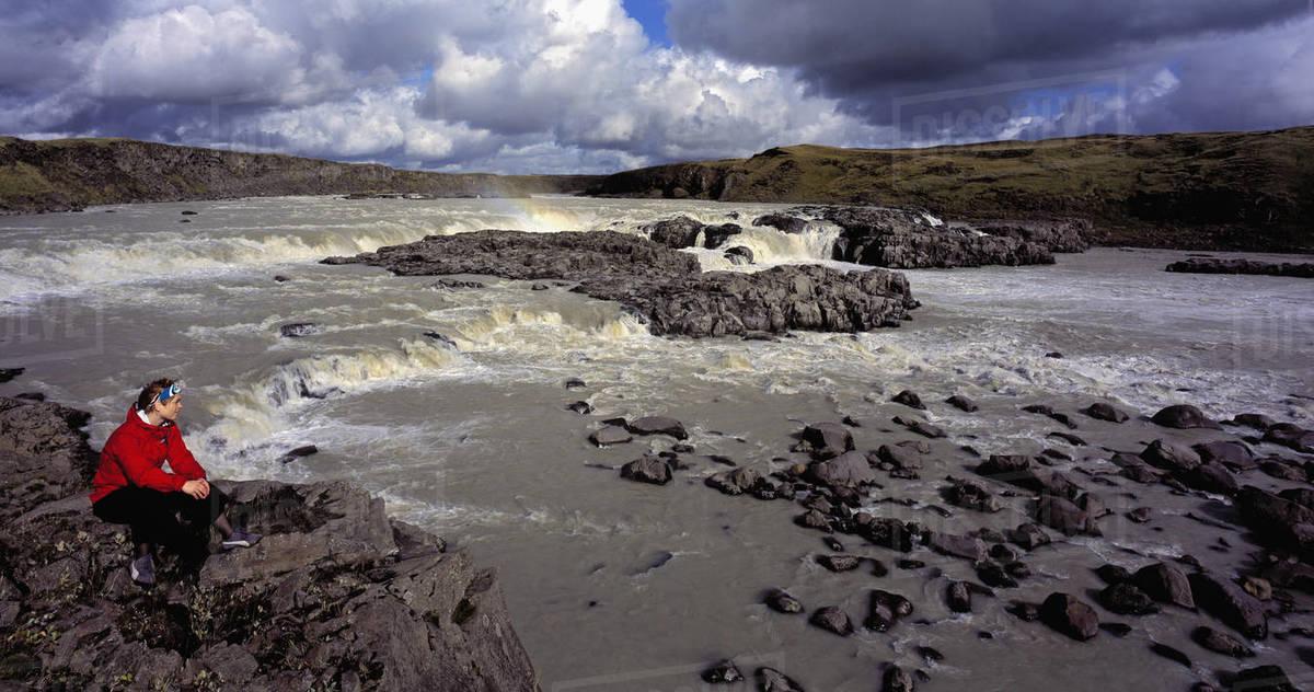 Woman admiring waterfall on the river Þjórsá in Iceland Royalty-free stock photo